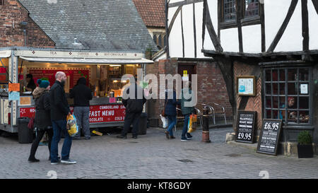 Customers buy street food & people with shopping bags walk through Shambles Market, an historic market area in York - Stock Photo