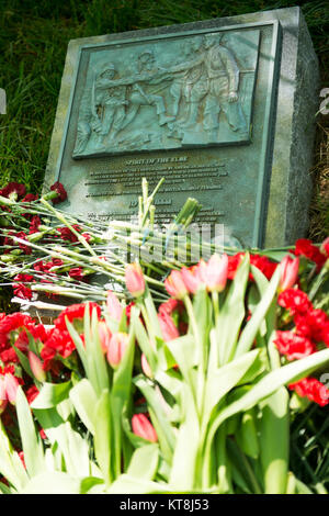 The Spirit of the Elbe marker is covered in flowers left by attendees of the annual wreath-laying ceremony in Arlington - Stock Photo