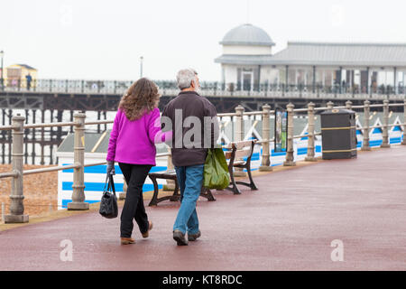 Hastings, East Sussex, UK. 22nd December 2017. A couple stroll arm in arm along the Hastings promenade on a damp - Stock Photo