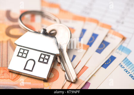 Key house shaped ring with euro money - Stock Photo
