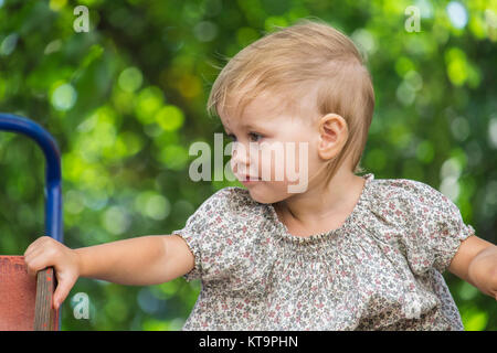 Baby sits on a childrens slide and looking to the right - Stock Photo