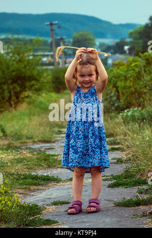 Little girl in a blue dress with spikelets of wheat in her hand is standing on the road and raising her hands upwards - Stock Photo