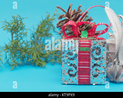 White shiny silver gift box with red ribbon and bow with white square and round shape gift box and pine cone and - Stock Photo