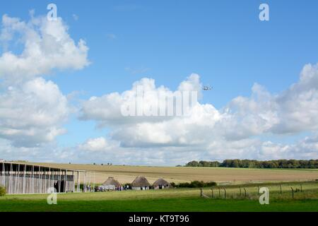 Military helicopter flying over the entrance to Stonehenge, near Amesbury, Wiltshire, England, UK - Stock Photo
