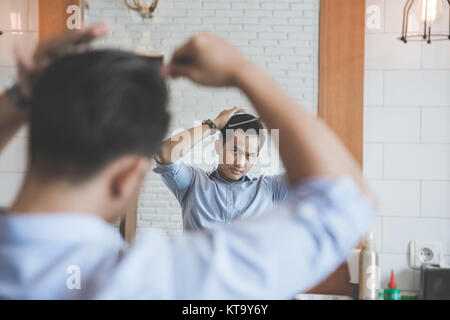 portrait of man combing his hair after having a cut at barbershop - Stock Photo