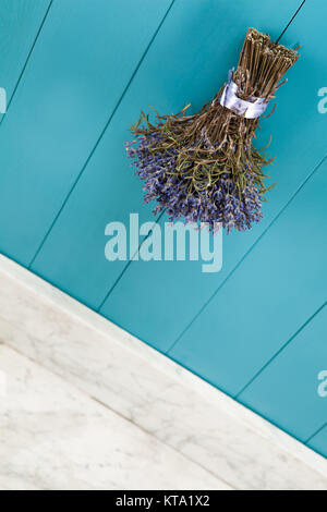 a bunch of lavender is hanging on a mediterranean-blue wooden wall to dry - Stock Photo
