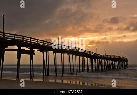 NC01145-00...NORTH CAROLINA - Colorful sunrise on a cloudy day at Avon Fishing Pier along the Outer Banks on Hatteras - Stock Photo