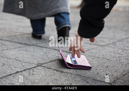 Man Picking Up A Lost Purse - Stock Photo