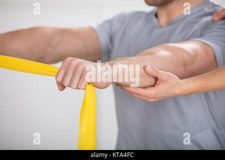 Physiotherapist Giving Man A Training With Exercise Band - Stock Photo