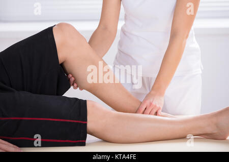 Physiotherapist Giving Knee Therapy In Clinic - Stock Photo