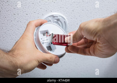 Person Removing Battery From Smoke Detector - Stock Photo