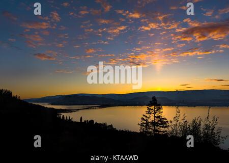 A view of a beautiful sunrise over the bridge over Okanagan Lake between West Kelowna and Kelowna Brititsh Columbia - Stock Photo