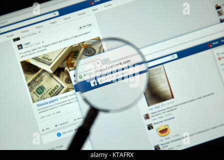 MONTREAL, CANADA - MARCH 25, 2016 - Facebook page under magnifying glass. Facebook is a corporation and online social - Stock Photo