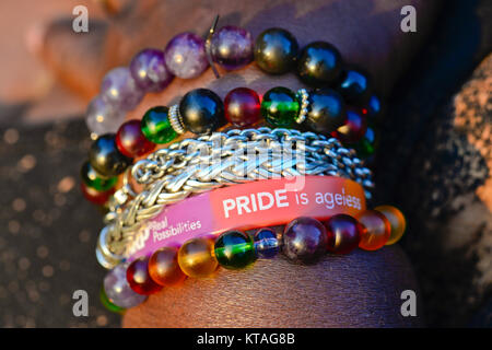 Colorful bracelets with gay pride bracelet worn by an African-American woman - Stock Photo