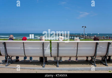 Elderlies sitting on bench with view to the pier, beach promenade of Binz, Ruegen island, Mecklenburg-Western Pomerania, - Stock Photo