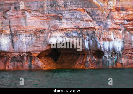 Naturally formed caves among the mineral seep sandstone cliffs on Lake Superior and Pictured Rocks National Lakeshore - Stock Photo
