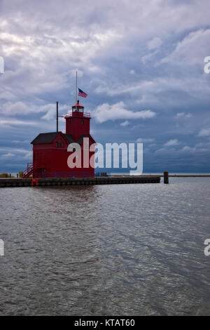 Autumn evening storm builds over the Holland Harbor Lighthouse know as Big Red at the entrance channel connecting Lake Michigan with Lake Macatawa in  Stock Photo