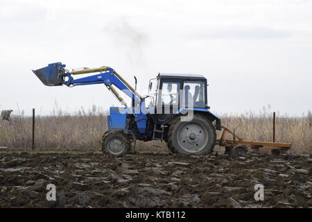 Tractor plowing the garden. Plowing the soil in the garden - Stock Photo
