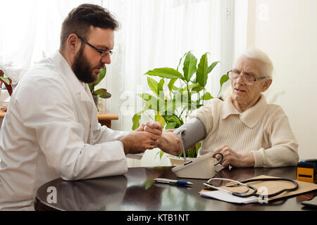 a private doctor's office. geriatrician doctor takes the patient and measures her blood pressure. - Stock Photo