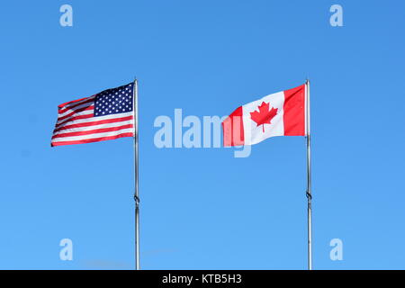 The flags of Canada and the US fly on a flag pole in Victoria BC. - Stock Photo