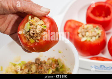Stuffed tomatoes preparation : Stuffing the emptied tomatoes - Stock Photo