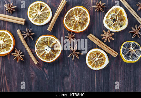 Circles of dried orange on a brown wooden surface - Stock Photo