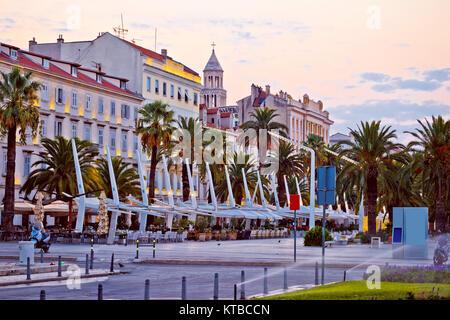 Split main waterfront walkway palms and architecture - Stock Photo