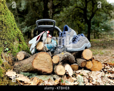 Shoes, protection gloves and glasses to safely use the chainsaw to cut wood in the forest. - Stock Photo