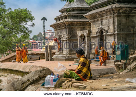 KATHMANDU, NEPAL MAY 15, 2017: Traditional holy men sadhu in hindu temple with old beautiful stupas of stone. - Stock Photo