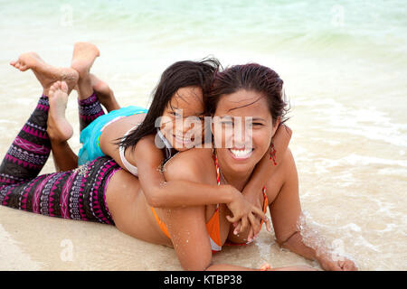 Filipino mother and daughter have fun together at the beach. The little girl lays on her mother's back as they play - Stock Photo