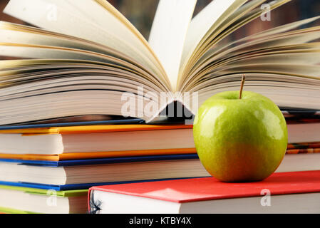 Composition with hardcover books and apple - Stock Photo