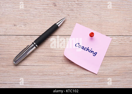 coaching word on pink sticky note and red pin - Stock Photo