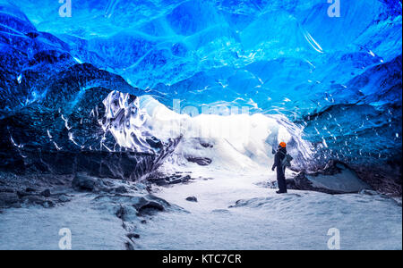 Traveler in ice cave, man standing underground inside of a glacier, climate specific, Vatnajokull National Park, - Stock Photo