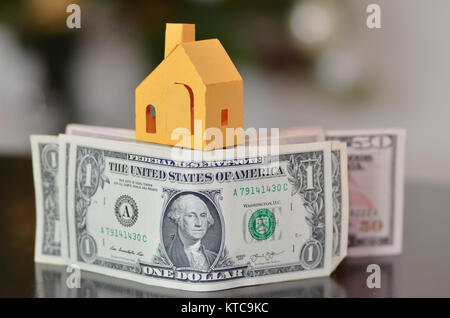 Miniature paper made house stand on  money - Stock Photo