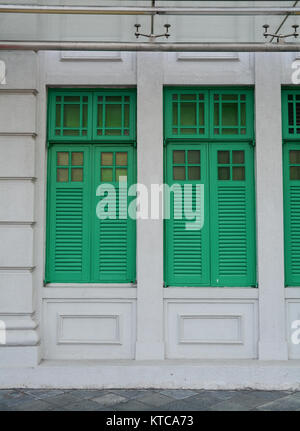 Green wooden doors at an old palace in Singapore. Singapore is global financial center with a tropical climate and - Stock Photo