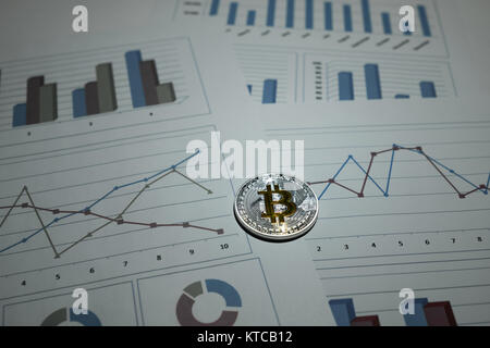 Metal bitcoin on business charts. Crypto currency. Virtual money. BTC - Stock Photo