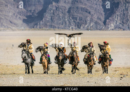 Kazakh eagle hunters arrive on horseback to the Golden Eagle Festival in Mongolia - Stock Photo