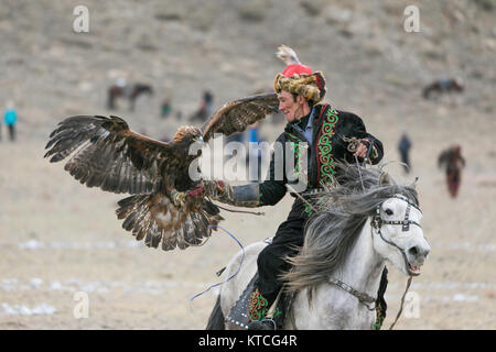 Kazakh eagle hunter on horseback competing at the Golden Eagle Festival in Mongolia - Stock Photo