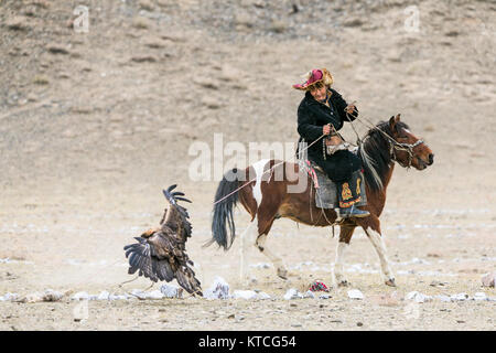 Kazakh eagle hunter on horseback competing at the Golden Eagle Festival in Mongolia - Stock Photo