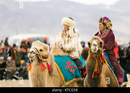 Aisholpan the Eagle Huntress and another camel rider at the Golden Eagle Festival in Mongolia - Stock Photo