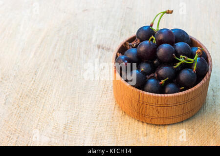 black currants in the bowl on a wooden stump - Stock Photo
