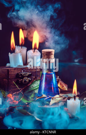 Magical still life with spells, herbs, potion ingredients, wax candles and a glass bottle with mystic liquid on - Stock Photo