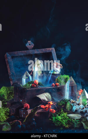 Magical still life with a wooden chest, potion bottle, crystals, moss, berries and leaves on a dark background. - Stock Photo