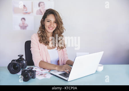 young photographer sitting on her office while working on laptop - Stock Photo