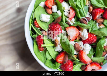 Fresh mixed green salad with spinach, strawberries, almonds and feta cheese. - Stock Photo