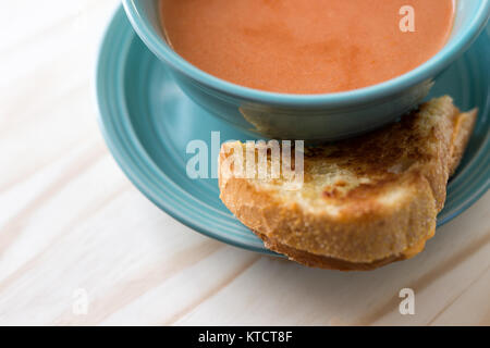 Grilled cheese sandwich with a bowl of hot tomato soup. - Stock Photo