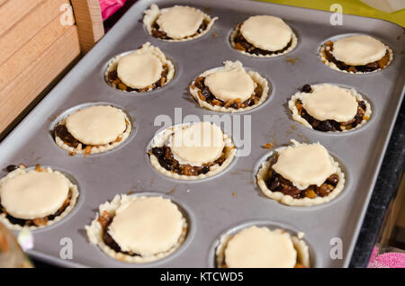Mince pies in a baking tin ready to put into the oven. They are a festive snack, traditionally eaten around Christmas. - Stock Photo