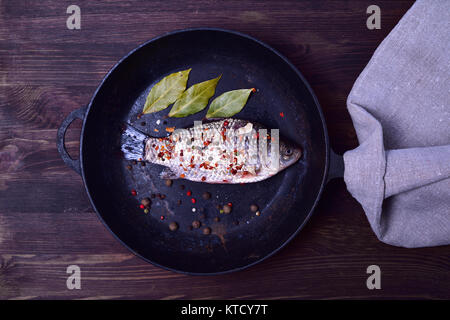 Crucian carp in spices on a black cast-iron frying pan - Stock Photo