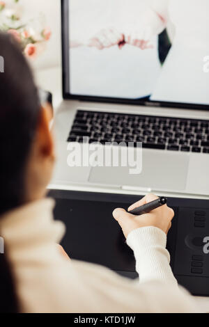 woman retouching on computer laptop using digital tablet and stylus pen - Stock Photo