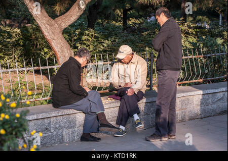 Two senior Chinese man play the chess and another one watching - Stock Photo
